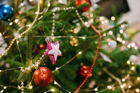Close-up of a pink Christmas tree toy in the shape of a star on the branches of a Christmas tree. Imagens - 156872418