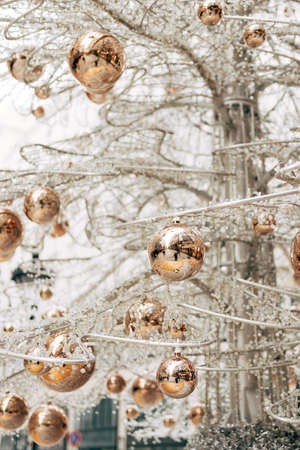 Gold glossy Christmas balls on a white glass Christmas tree.