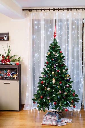 Decorated Christmas tree in the interior of the room with wrapped gifts underneath. 스톡 콘텐츠
