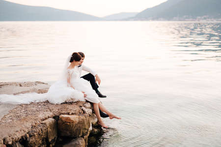 the bride and groom sitting on the pier and bride swinging her feet in the water