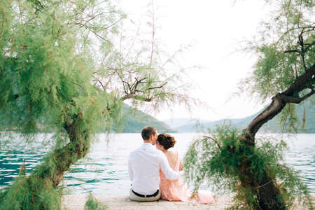 bride and groom are sitting among trees and hugging on the pier in Perast Imagens