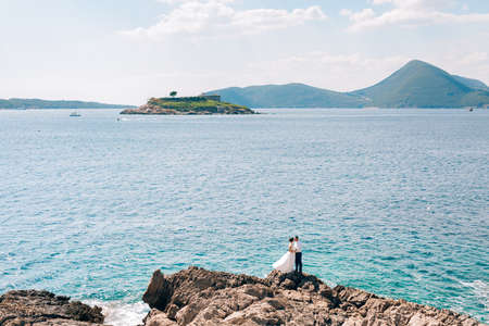 bride and groom are hugging on the beach of the Mamula island against the backdrop of the Arza fortress