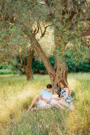 beautiful happy family in the olive grove sitting under the tree in Montenegro