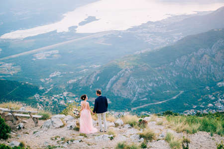 bride and groom standing on the mountain against the backdrop of the Bay of Kotor