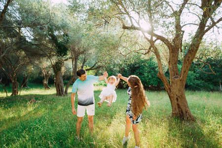 parents hold the childs hands and toss in the olive grove in Montenegro