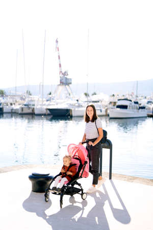 Woman pushing a pink stroller on a boat pier on a sunny day