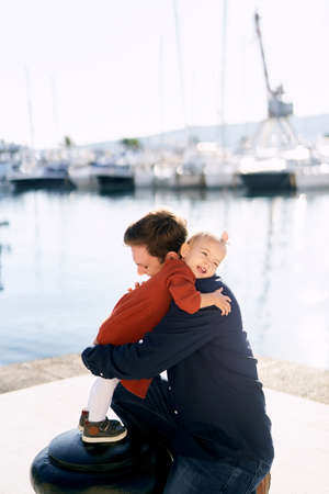 Baby girl is hugging her daddy while having a family day by the sea Imagens - 159183604
