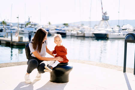 Woman smiling at her baby-girl while having a walk in a boat marina