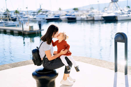 Mother is kissing her baby girl while sitting on a pier by the sea