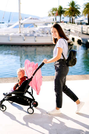 Mother and daughter in a pinl stroller walking in a boat marina Imagens