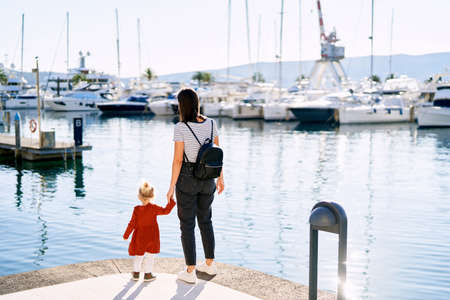 Mother is holding her daughters hand and looking at boats in Porto Montenegro