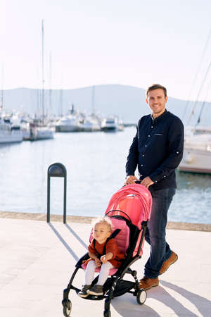 Man is pushing his daughter in a pink stroller on a boat pier