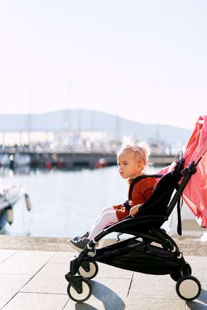 Little girl in a terracotta dress and white tights is sitting in a pink stroller on a pier Imagens