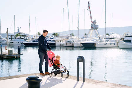 Dad is pushing a pink stroller with his daughter sitting inside while having a family day by the sea Imagens