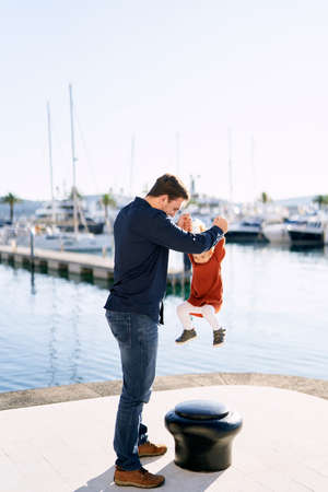 Father is playing with his daughter at a boat marina