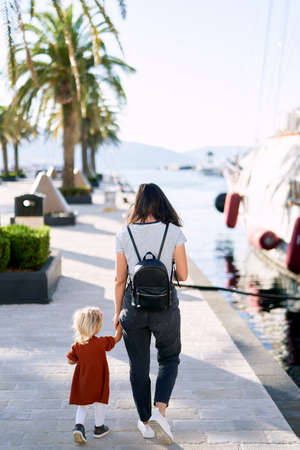 Mother and daughter are walking hand in hand on a boat pier in Porto Montenegro