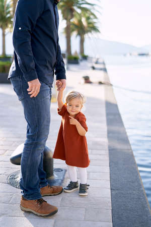 Father and daughter are walking hand in hand by the sea on a sunny day