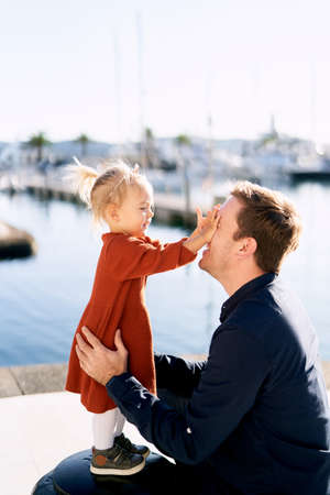 Little girl is playing peek-a-boo with her daddy on a boat marina Imagens - 159185117