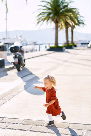 Cute 18-month old girl in a terracotta dress and white tights is running on a boat pier on a sunny day