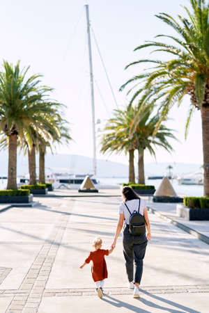 Woman is walking hand in hand with her 2 year old daughter among palm trees on a boat pier