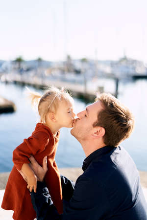 Cute 2-year old is kissing her daddy while taking a walk on a sunny day Imagens - 159185127