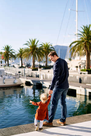 A 2-year old is walking with her dad on a boat pier on a sunny day
