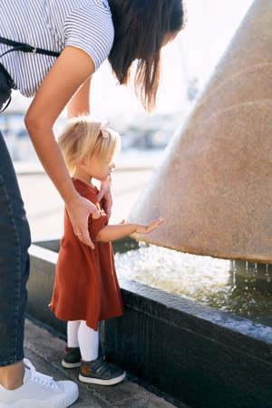 A cute toddler is playing by the fountain with her mother on a sunny day Imagens