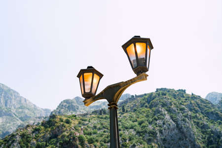 Glowing street lamp against the background of mountains and sky close-up.
