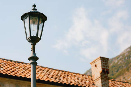 High street lamp at the level of the roof of the house against the background of mountains and sky.