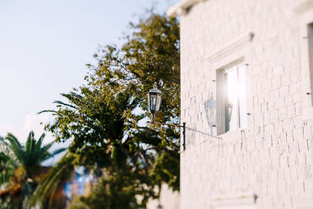 Street hanging lamp on a house on a sunny day. Perast town in Montenegro. Imagens