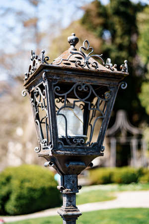 Close-up of a street lamp with a metal body with patterns in the park. Imagens