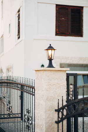 Included street lamp in black on a column of a metal fence near a white building. Imagens