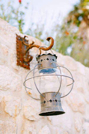 Old metal hanging lantern on a rusty hook on a stone wall. Imagens - 159185289