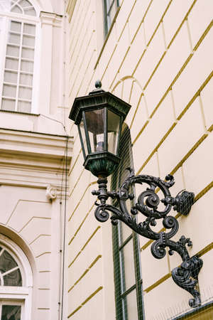 Street hanging lamp with a beautiful bracket in the wall of a multi-storey building. Imagens - 159185290