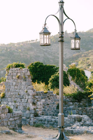 A tall gray street lamp among ancient stone ruins, hills and green vegetation. Imagens - 159185291