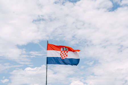 Croatian flag waving in the wind against the sky. Imagens