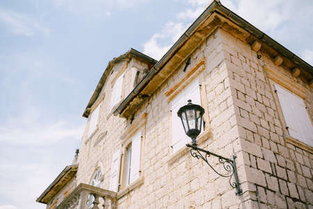 Hanging street lamp on the wall of the building near the balcony and roof windows. Imagens