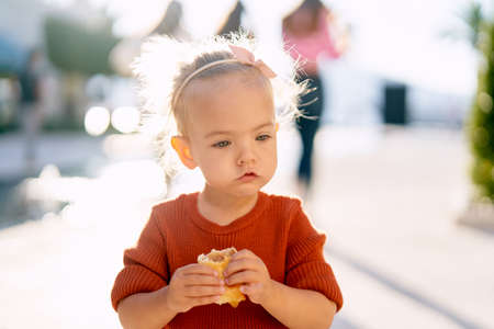 Cute baby girl is eating a pie by the fountain in the park