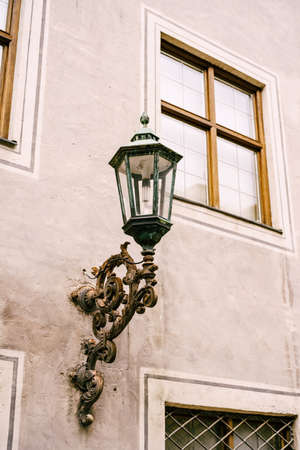 An old residential building with a bracket in the wall for a street lamp in the daytime.