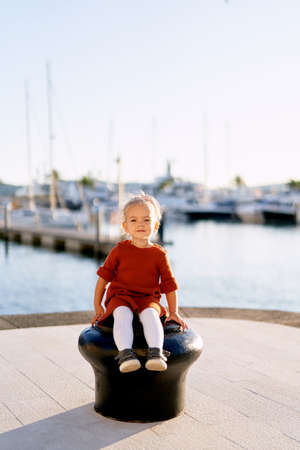 A portrait of a pretty 2-year old girl sitting on a boat pier by the sea