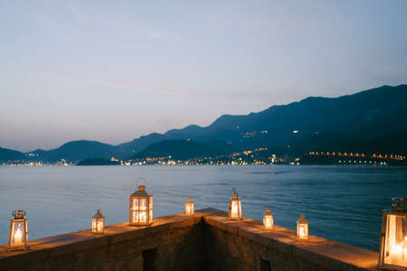 Candlesticks-lanterns on a stone border overlooking the mountains and the coast of Montenegro in the city of Budva.