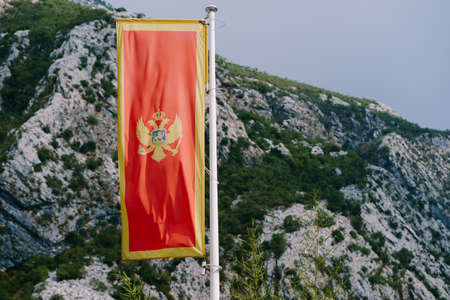 Red flag of Montenegro with a double-headed eagle against a background of mountains.
