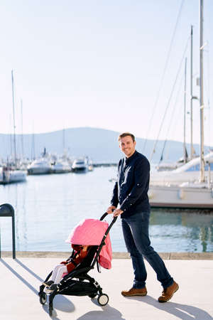 Man is pushing a pink stroller with his baby girl sitting inside