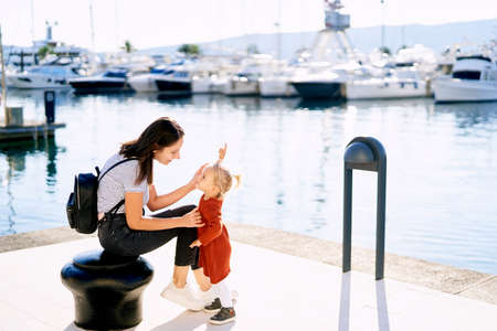 Mother is talking to her sweet 2-year old daughter while sitting on a pier