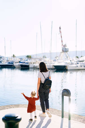 Little girl is looking at the boats with her mother