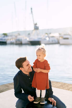 Father is smiling at his daghter on a boat pier by the sea