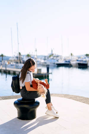 Mother and daugher are playing while sitting on a pier in Porto Montenegro