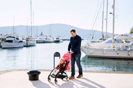 Father is pushing a pink stroller with his baby girl sitting inside at a boat marina
