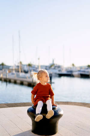 Cute little baby girl in a terracotta dress and white tights is sitting on a boat pier by the sea