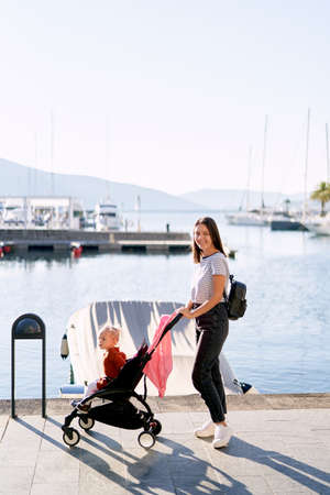 Mother is pushing her toddler in a pink stroller on a boat pier in marina
